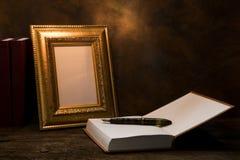 ainda vida da moldura para retrato na tabela com livro do diário Imagens de Stock Royalty Free