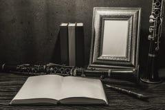 Ainda vida da moldura para retrato na tabela de madeira com clarinete Imagens de Stock