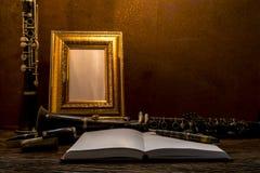 Ainda vida da moldura para retrato na tabela de madeira com clarinete Fotografia de Stock