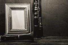 Ainda vida da moldura para retrato na tabela de madeira com clarinete Foto de Stock