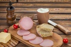 Ainda vida da salsicha fervida cortada com ingredientes café da manhã rural - salsicha fervida, pão, leite, manteiga, tomates Fotografia de Stock Royalty Free