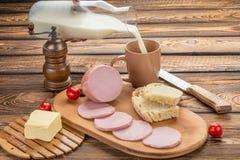 Ainda vida da salsicha fervida cortada com ingredientes café da manhã rural - salsicha fervida, pão, leite, manteiga, tomates sob Imagens de Stock