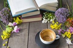 Ainda vida das flores e do livro, copo de café vazio em vagabundos de madeira imagens de stock