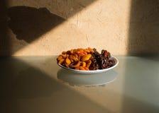 Ainda vida - datas secadas, caqui e ameixas secas em uma placa branca foto de stock