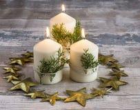 Ainda vida de três velas que queimam-se com ramos verdes Fotos de Stock Royalty Free
