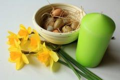 Ainda vida - decoração da Páscoa - daffodiles, ovos em uma cesta e vela verde Imagens de Stock