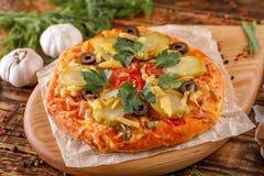 Ainda-vida deliciosa, pizza caseiro quente com verdes em uma placa de madeira na tabela Fotos de Stock