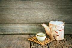 Ainda vida do grupo de bule e de copo cerâmicos japoneses em t de madeira Foto de Stock
