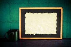 Ainda vida do papel queimado vazio posto sobre o quadro-negro com café c Imagem de Stock Royalty Free