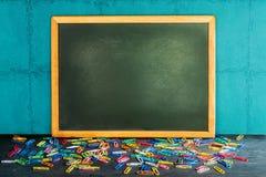 Ainda vida do quadro-negro vazio e de clipes de papel coloridos no woode Imagens de Stock
