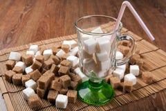 Ainda vida dos cubos do branco e do açúcar mascavado em um vidro e na Foto de Stock Royalty Free