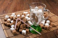 Ainda vida dos cubos do branco e do açúcar mascavado em um vidro e na Imagem de Stock