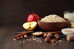 Ainda vida dos ingredientes para a dieta saudável: a aveia lasca-se na bacia com maçã, canela, porcas, mel, leite na tabela de ma Imagem de Stock