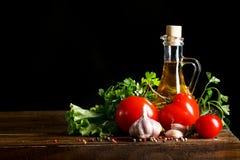Ainda vida dos tomates, do alho e do azeite em placas de madeira Em um fundo preto Fotos de Stock