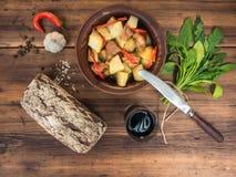 Ainda vida dos vegetais, de batatas cozidas com carne, de vegetais, de pão e de vidro do vinho tinto no fundo de madeira Imagem de Stock Royalty Free