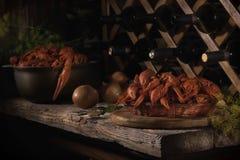 Ainda vida em cores escuras na adega de vinho com lagostas vermelhas foto de stock