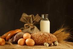 Ainda vida em uma tabela com ovos, pão e uma garrafa do leite, espaço da cópia para seu texto Imagens de Stock