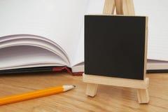 Ainda vida, etiqueta de madeira do quadro sobre o caderno aberto Fundo de madeira da tabela Copie o espaço imagem de stock