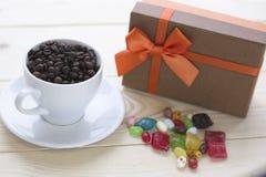 Ainda vida festiva com uma caixa de presente, copo do coffe com uns pires Fotografia de Stock