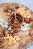 Ainda vida, frasco de madeira dos doces, porcas, queijo, uvas imagens de stock