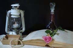 Ainda vida horizontal em um fundo preto com um livro, uma lanterna velha e uma garrafa do vinho, um cor-de-rosa aumentou mentiras Imagens de Stock