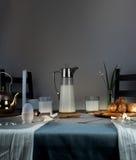 Ainda vida 1 Jantar rústico jarro de leite, velas, chá, ovos, rolos de pão na tabela Foto de Stock Royalty Free