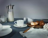 Ainda vida 1 Jantar rústico jarro de leite, velas, chá, ovos, rolos de pão na tabela Fotografia de Stock