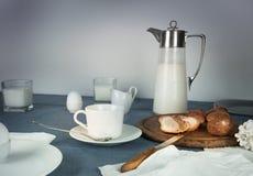 Ainda vida 1 Jantar rústico jarro de leite, velas, chá, ovos, rolos de pão na tabela Fotos de Stock Royalty Free