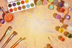 Ainda vida, mostrando um interesse na pintura e na arte da aquarela Muitas escovas, frascos com aquarela pintam e usaram a mentir Foto de Stock Royalty Free