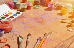 Ainda vida, mostrando um interesse na pintura e na arte da aquarela Muitas escovas, frascos com aquarela pintam e usaram a mentir Foto de Stock