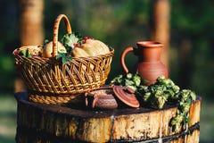 Ainda vida na natureza de um jarro da argila, trigo em um potenciômetro, lúpulos em uma plataforma de madeira, cestas com uma abó Fotografia de Stock