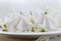 Ainda a vida no estilo do vintage com beijos e cereja de merengue floresce na tabela de madeira oxidada Fotografia de Stock Royalty Free