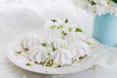 Ainda a vida no estilo do vintage com beijos e cereja de merengue floresce na tabela de madeira oxidada Foto de Stock