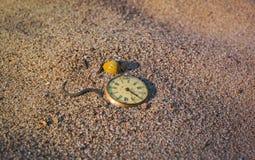 Ainda vida - o relógio de bolso podre antigo enterrou parcial na areia no por do sol Fotografia de Stock Royalty Free
