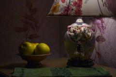 Ainda vida pela luz da lâmpada, um vaso com maçãs dentro Foto de Stock