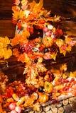 Ainda a vida que consiste na grinalda de vime, folhas alaranjadas, outono seja Fotografia de Stock