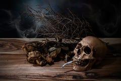 Ainda vida que fuma o crânio humano com o cigarro na tabela de madeira Foto de Stock