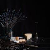 Ainda vida 1 queijo duro, grupo da alfazema, faca antiga na tabela de madeira Fundo preto Imagem de Stock Royalty Free
