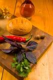ainda vida - queijo nacional caseiro em uma placa de corte com uma faca, manjericão de Adyghe, salsa, cal, óleo de sésamo, piment imagens de stock
