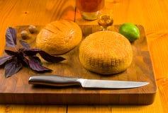 ainda vida - queijo nacional caseiro em uma placa de corte com uma faca, manjericão de Adyghe, salsa, cal, óleo de sésamo, piment foto de stock royalty free