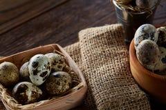 Ainda vida rústica com os ovos de codorniz na cubeta, na caixa e na bacia em um guardanapo de linho sobre o fundo de madeira, foc Fotografia de Stock