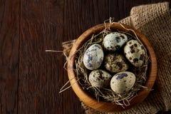 Ainda vida rústica com os ovos de codorniz na cubeta, na caixa e na bacia em um guardanapo de linho sobre o fundo de madeira, foc Imagens de Stock
