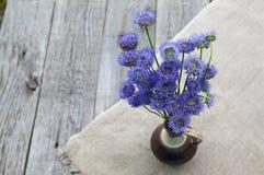 Ainda vida rústica com um ramalhete de flores azuis em um CCB de madeira Foto de Stock Royalty Free