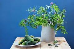 Ainda vida rústica com um ramalhete e uns pepinos frescos Fotos de Stock Royalty Free