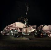Ainda vida rústica o galho seco em um vaso de vidro, rosa drapeja e frascos em uma tabela de madeira Fundo preto Fotos de Stock Royalty Free