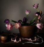 Ainda vida rústica ramalhete das tulipas em uma bacia de cobre na tabela de madeira Fundo preto Fotos de Stock