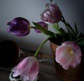 Ainda vida rústica ramalhete das tulipas em uma bacia de cobre na tabela de madeira Fundo preto Imagens de Stock