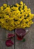 Ainda vida, ramalhete de flores amarelas, copo transparente do chá Fotografia de Stock