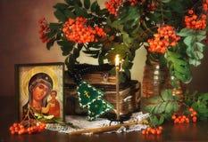 Ainda vida religiosa com um ícone da mãe e de Rowan santamente Imagem de Stock