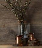 Ainda-vida Rua Ligth os copos de medição de cobre em círculos de madeira com salgueiro ramificam em uma tabela de madeira imagem de stock royalty free